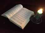 picture of hymnal open to Silent Night with a candle beside it
